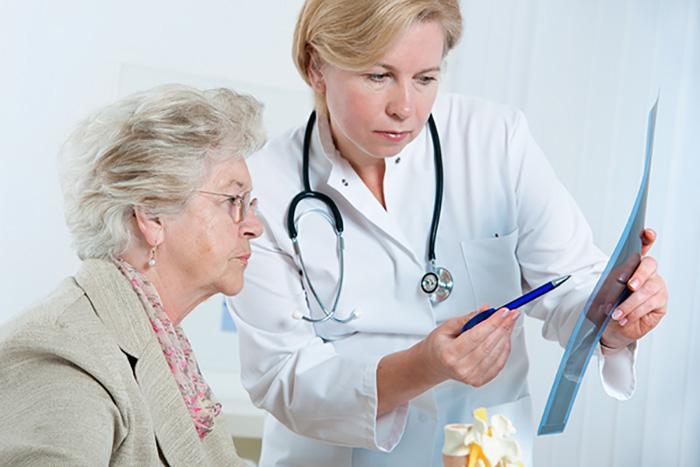 врач показывает рентген пожилой женщине